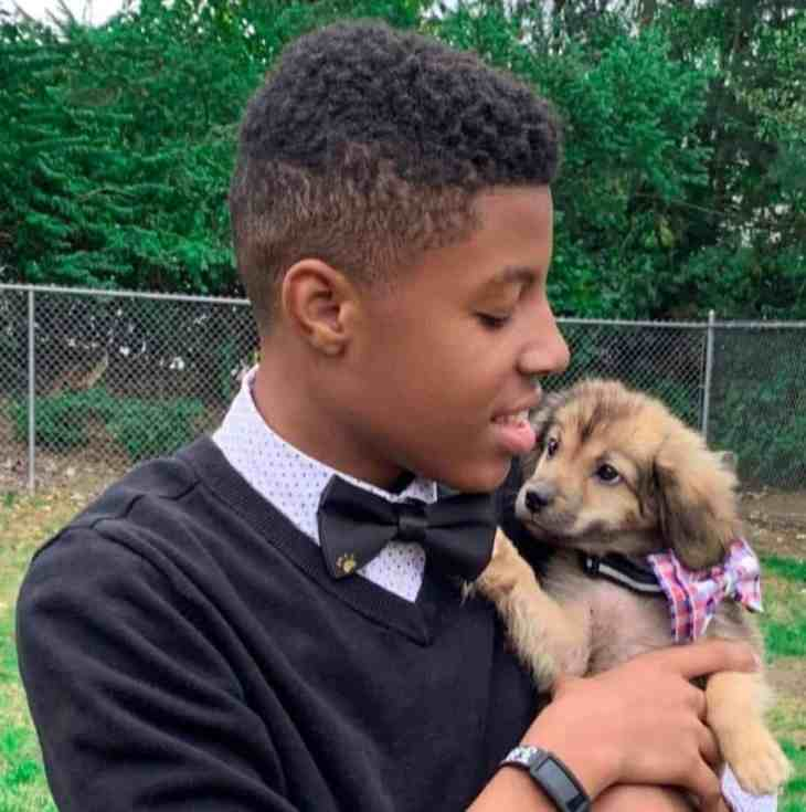 Darius Brown holding a puppy wearing a bow tie