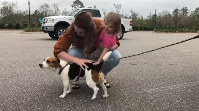 Brooke Lake and her daughter petting Lilly the beagle