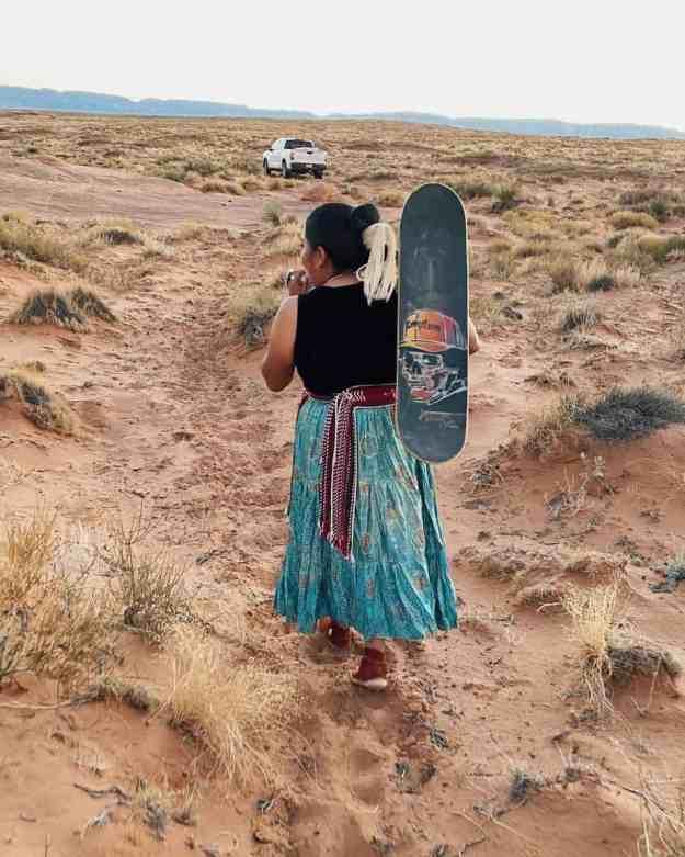 Naiomi Glasses holding her skateboard