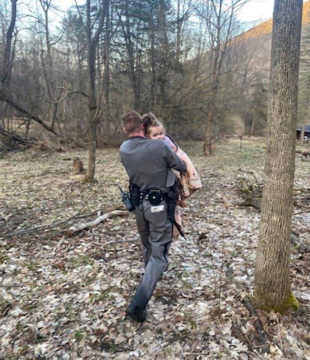 Trooper Brian Hotchkiss going down the hill while carrying a little girl in his arms