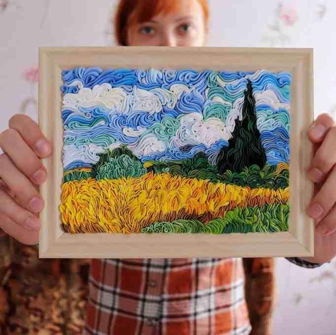 Алиса Ларюшкина держит в руках одну из своих работ из полимерной глины в рамке