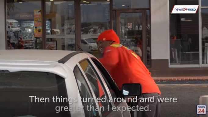 Нкосихо Мбеле протирает лобовое стекло автомобиля