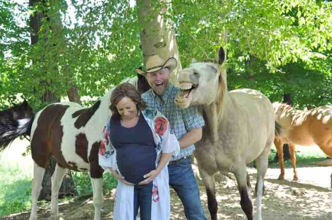 Amanda Eckstein and Phillip Werner posing a photo with their horse Buckshot during a maternity photoshoot