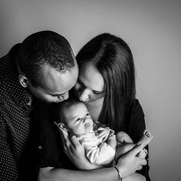 Michael Kahin and Erin Kahin kissing newborn Zane on the head