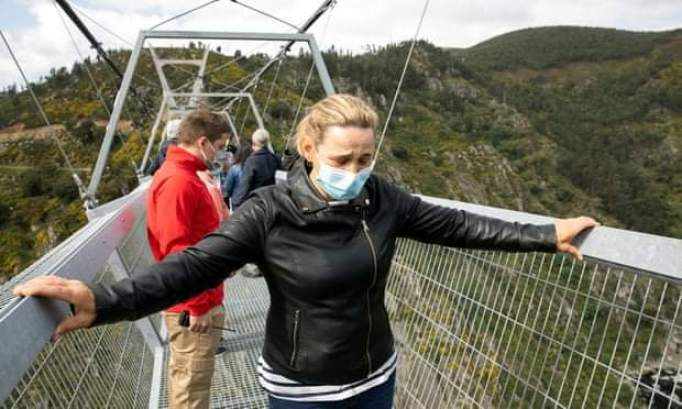 woman grips both sides of the bridge