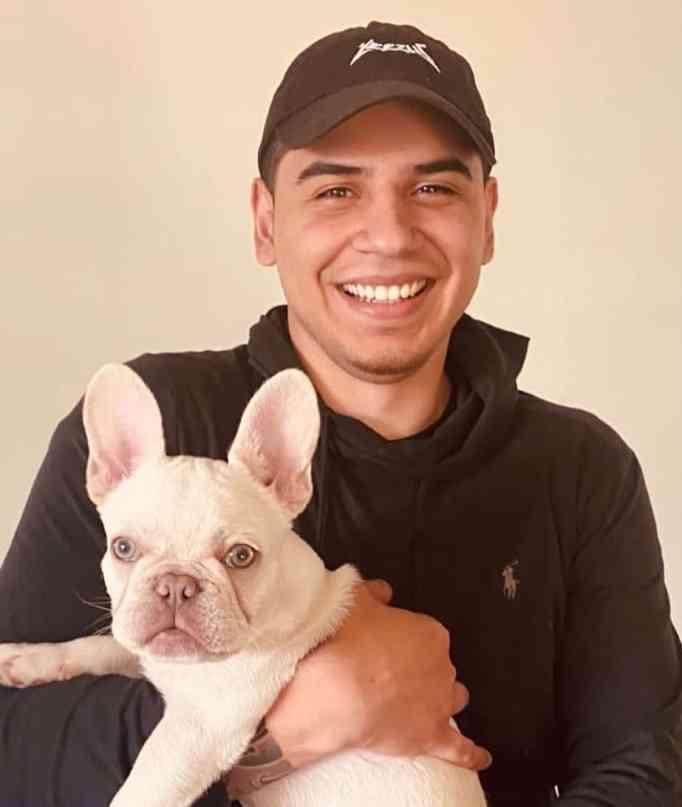 Devon Rodriguez carrying a French bulldog