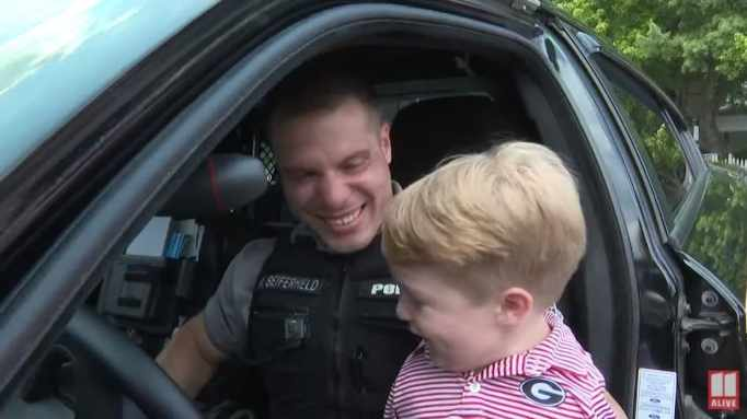 Officer Rolf Seiferheld and Harrison Humphries in the cop's patrol car