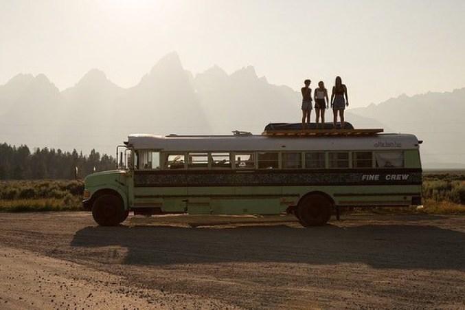 Three women standing on top of a school bus