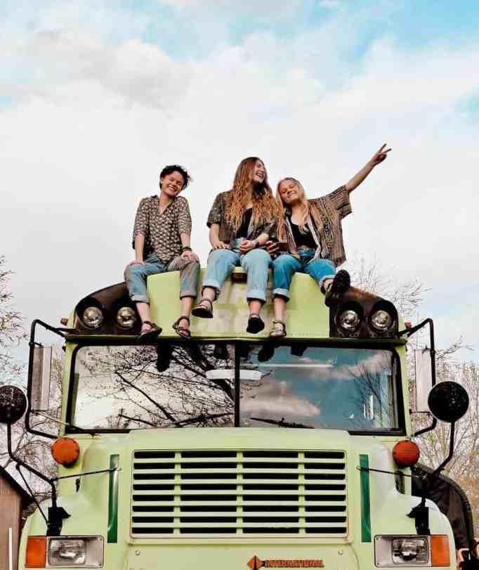 Three women sitting on top of a school bus
