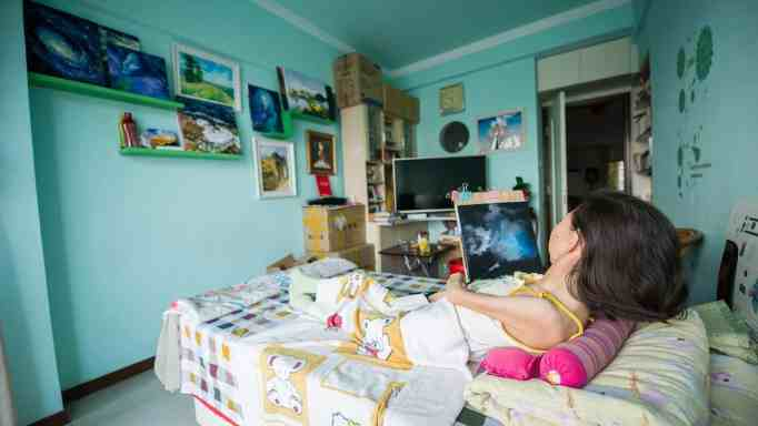 Zhang Junli hard at work in her room painting artworks.