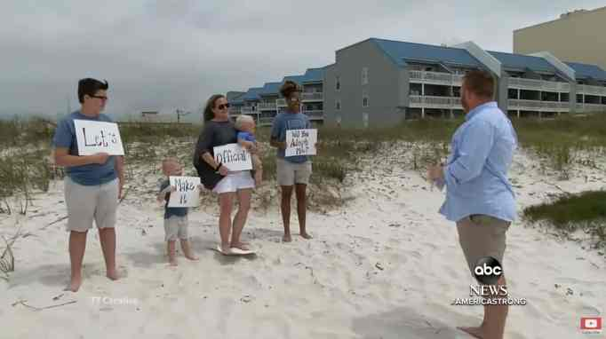 The Donaldson family and Alecia holding up signs as Daniel Donaldson reads them