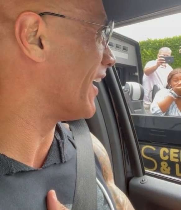 Dwayne Johnson talking to a group of tourists from his car