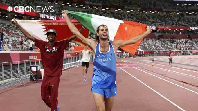 Gianmarco Tamberi and Mutaz Barshim parading their countries' flags during the Tokyo Olympics