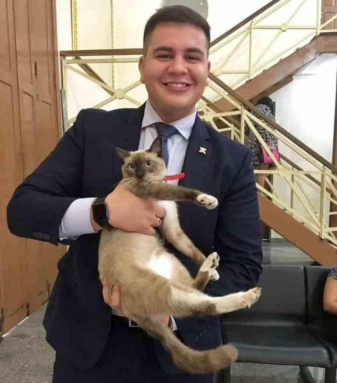 A man in a suit carrying Leon the lawyer cat