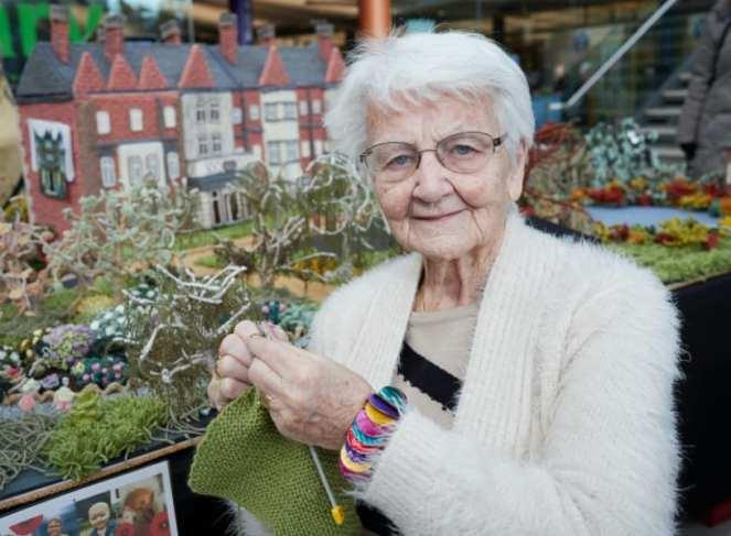 Margaret Seaman posing in front of her knitted Sandringham Estate replica