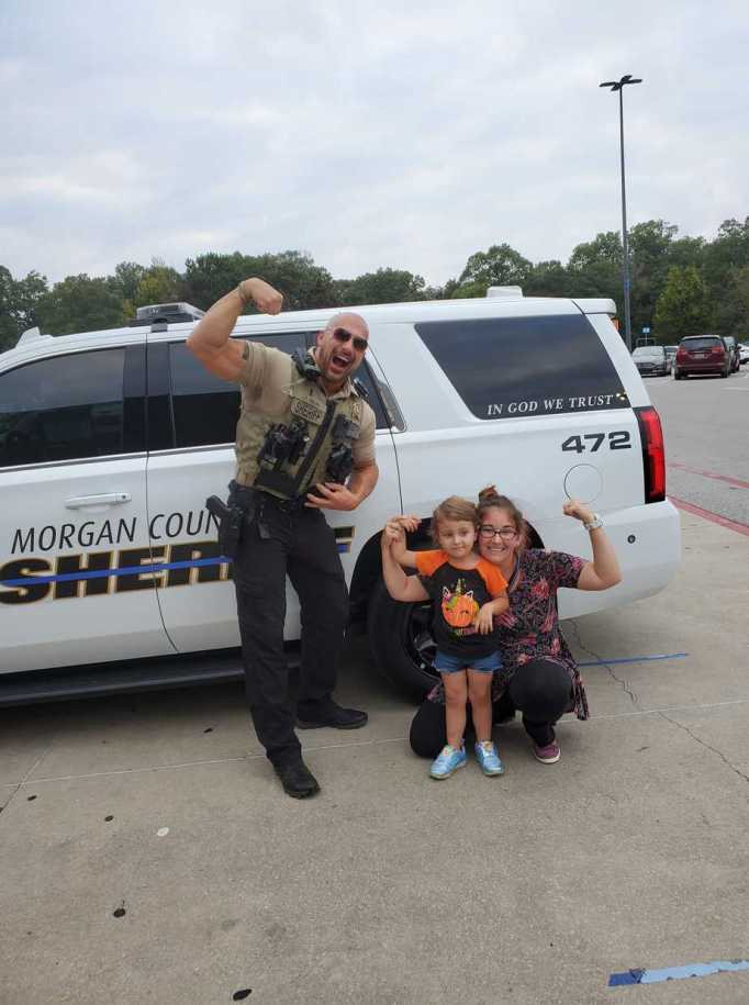 Patrol Lieutenant Eric Fields posing with a mom and her daughter