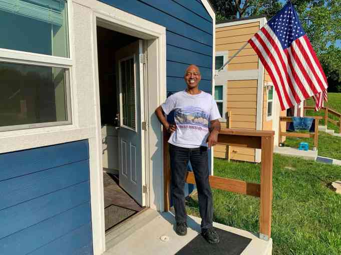 A veteran on the porch of his home in the VCP Village