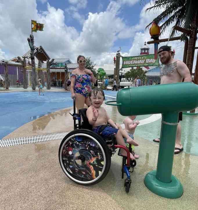 Child in wheelchair enjoys the splash pad.