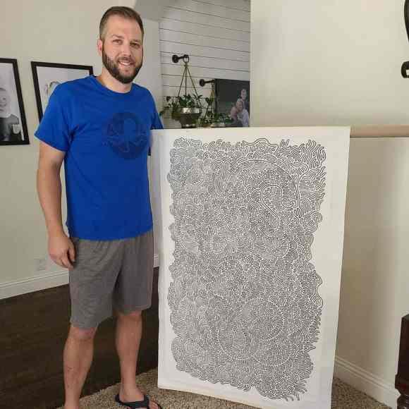 Tyler Foust holding up his artwork