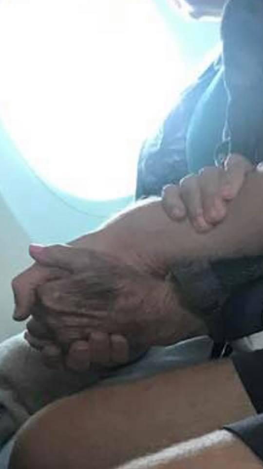 An elderly woman holding a man's hand during a flight