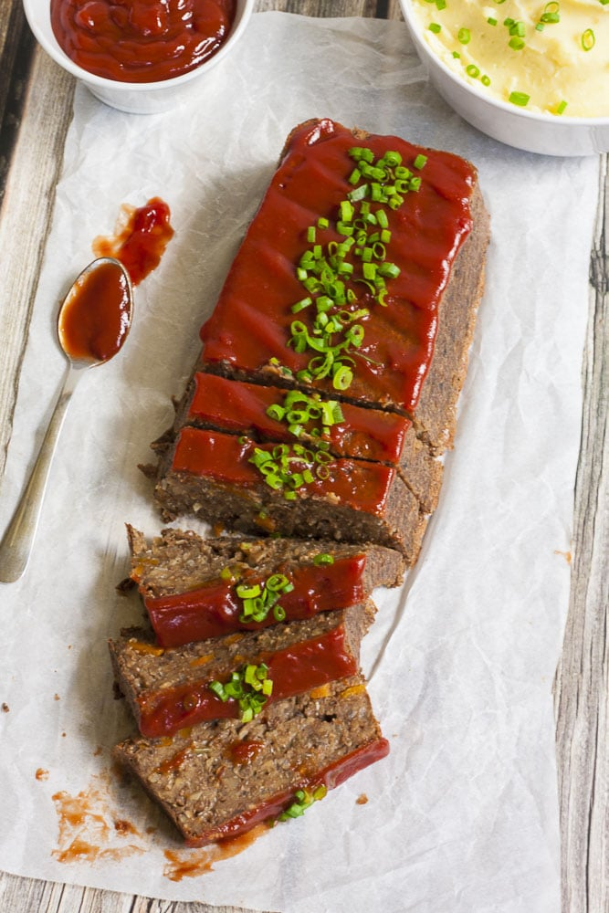 Vegan lentil loaf (partially sliced) on parchment paper from above with maple tomato glaze and chopped spring onion.