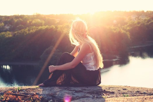 Young woman sitting on hill top watching down the river flowing