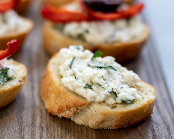 Almond ricotta with fresh herbs spread on toasted baguette