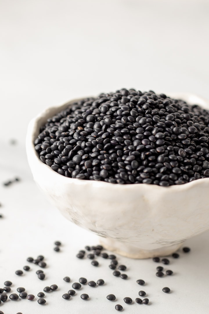 Dried black lentils in a small white bowl