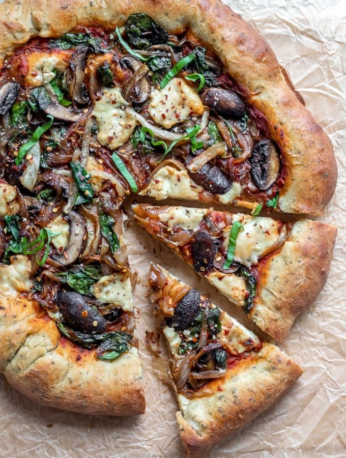 Vegan stuffed crust pizza topped with warm, melted cheese, onions and mushrooms