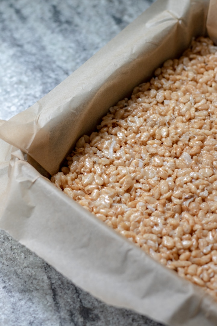 pressing rice krispie treat mixture into an 8x8 pan