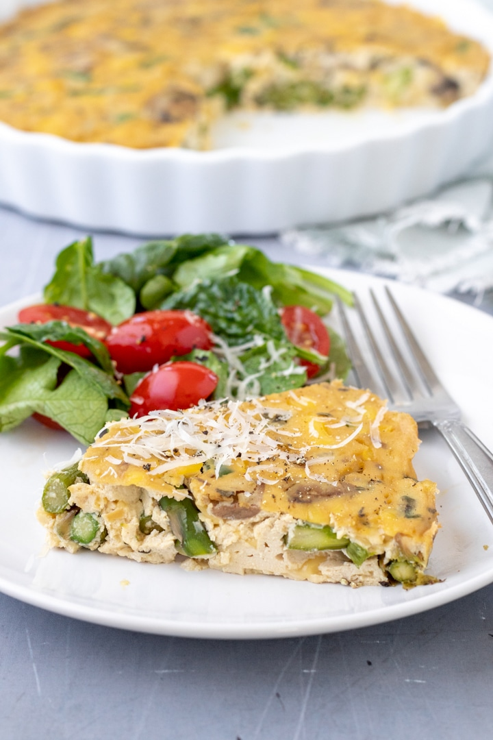 a slice of tofu quiche and a side salad on a plate