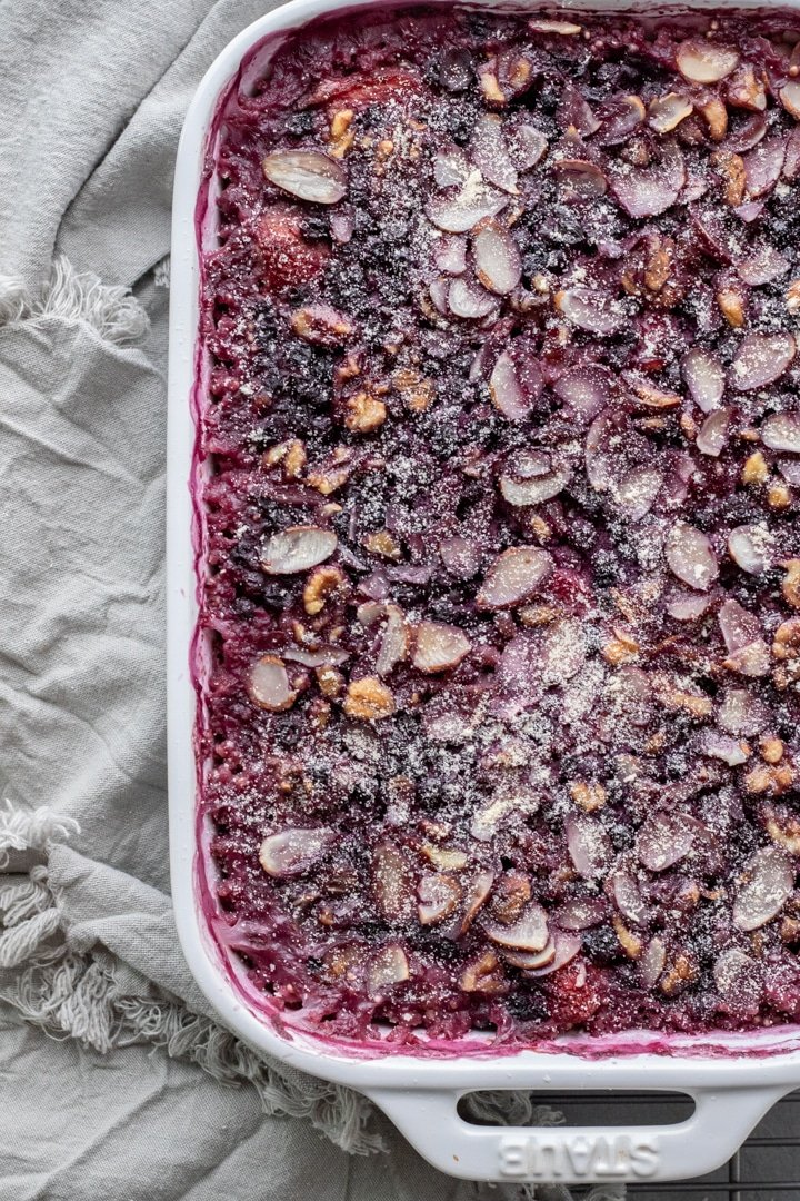 Millet Breakfast Bake With Berries in a white dish sprinkled with coconut flour