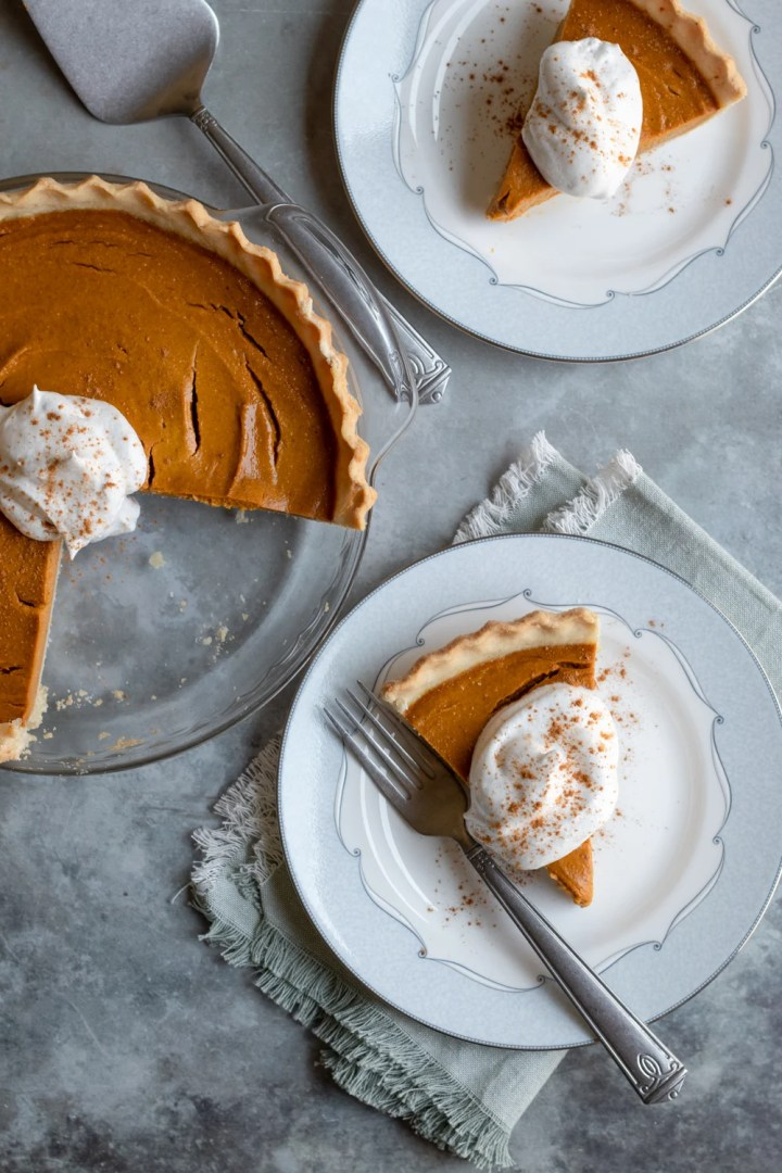 healthy pumpkin pie and 2 slices on plates with vegan whipped cream