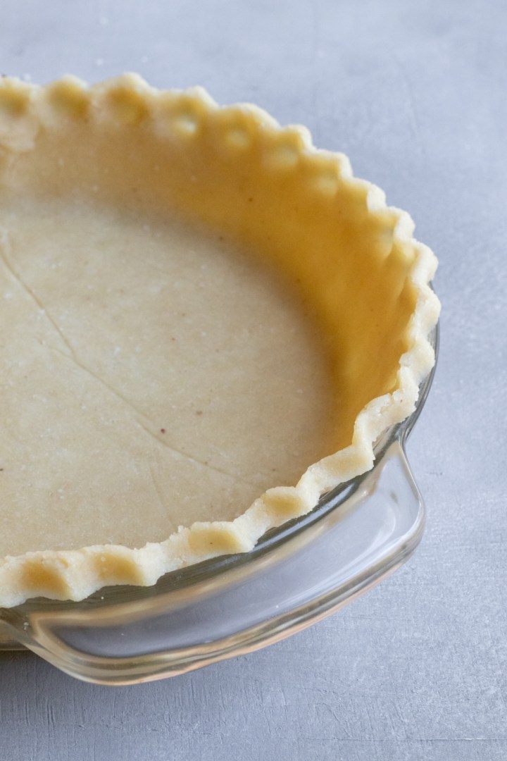 showing the crimped edge of gluten free vegan pie crust in a glass pie plate