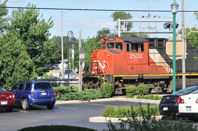 A Canadian National train rumbles through the Milwaukee Avenue crossing  with its horn blaring in July. City officials recently learned their request to reinstate a train horn quiet zone in the city has been approved. (Photo by Ed Nadolski)
