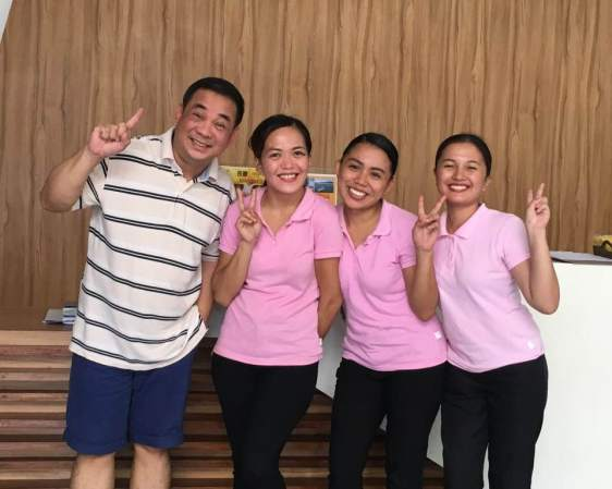 General Manager of Ferra Hotels with three Hospitality Students wearing pink shirts