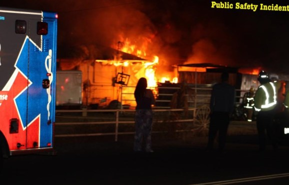 Bystanders watch as the barn and shed burn. Robert Carter photo