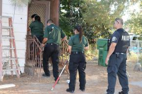 City of Corona animal control and police officers prepare to enter a residence where nearly three dozen dogs and small puppies were recovered. City of Corona photo