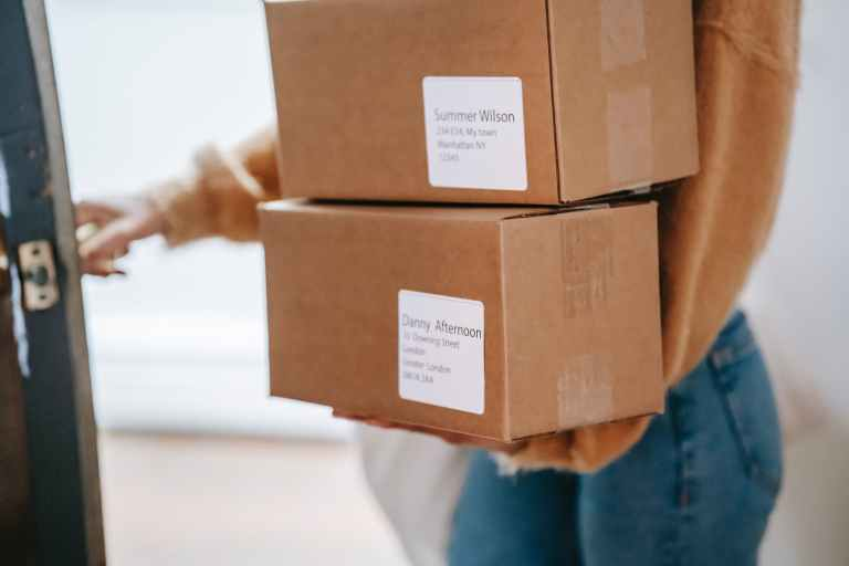 crop unrecognizable woman carrying boxes and entering post office