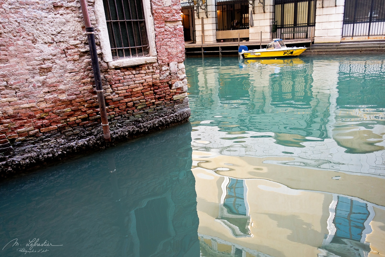 reflection of houses in a canal in Venice Venezia Italy with a speed boat parked in the back