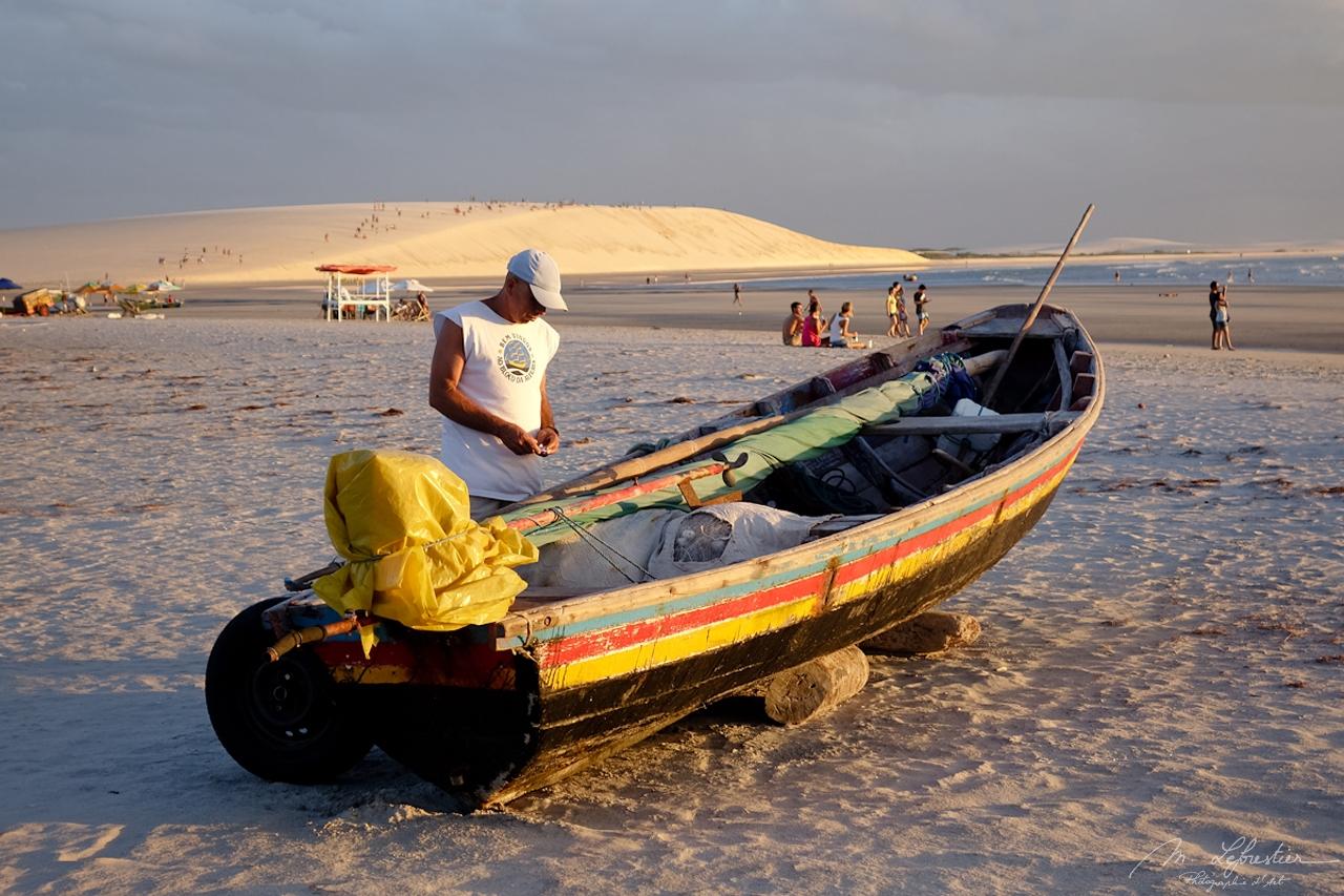 man with his boat on the Jericoacoara beach in Brazil