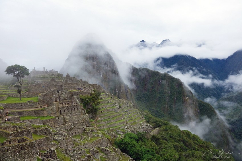 Machu Picchu with the mountains in the back covered in clouds
