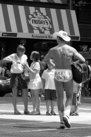 Naked Cowboy playing guitar in Times Square, New York City NYC USA in black and white