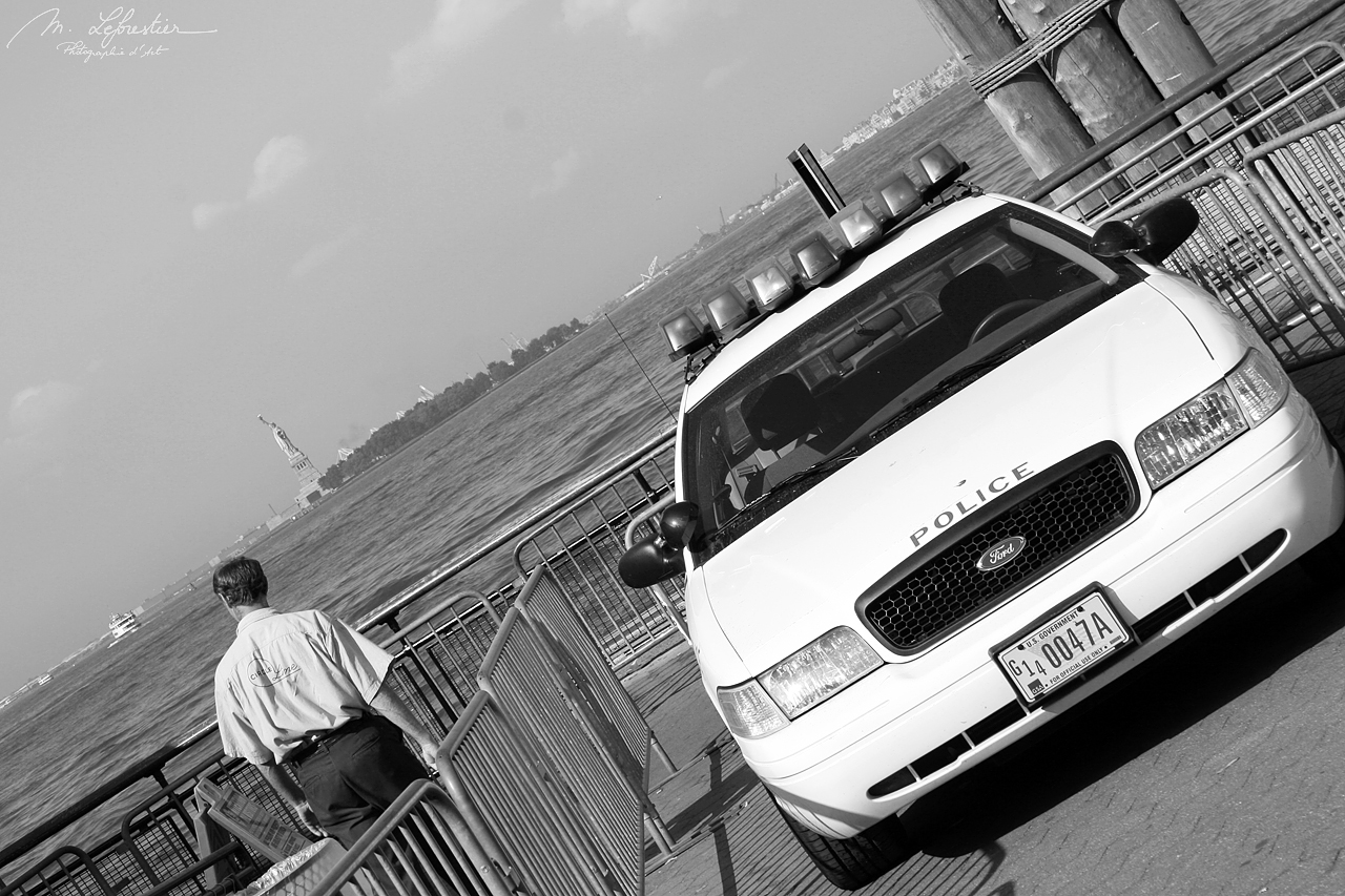 police car and officer watching the statue of liberty in Ellis island NYC USA black and white