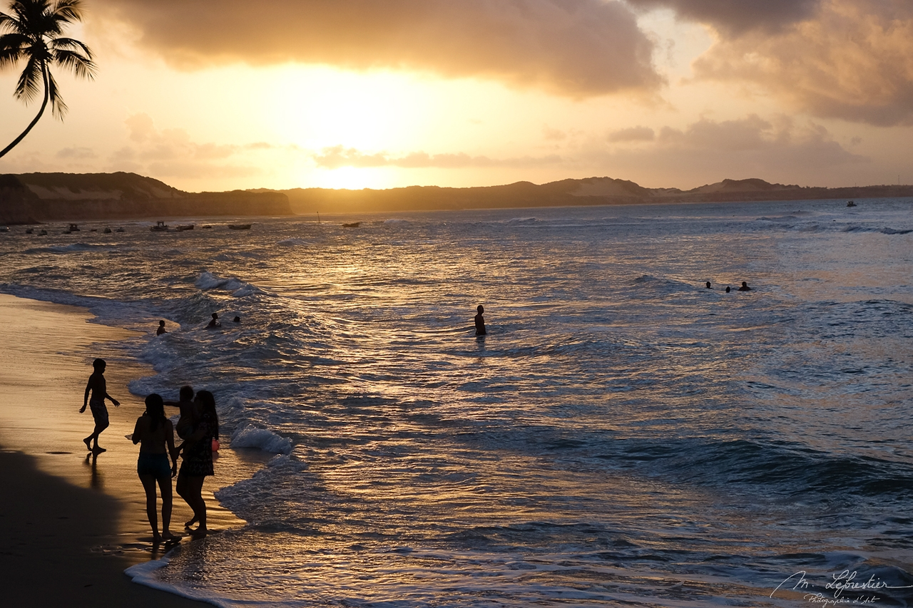 people in the sea at sunset at Baia dos Golfinhos in Brazil
