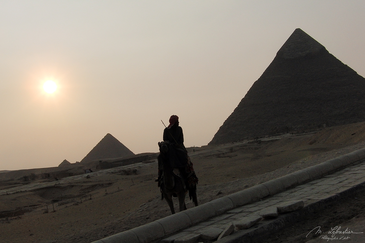 local on a horse at sunset in front of the aligned pyramids of Giza