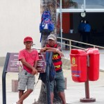 two red litter bins in Recife Brazil with two men with matching shirts nearby