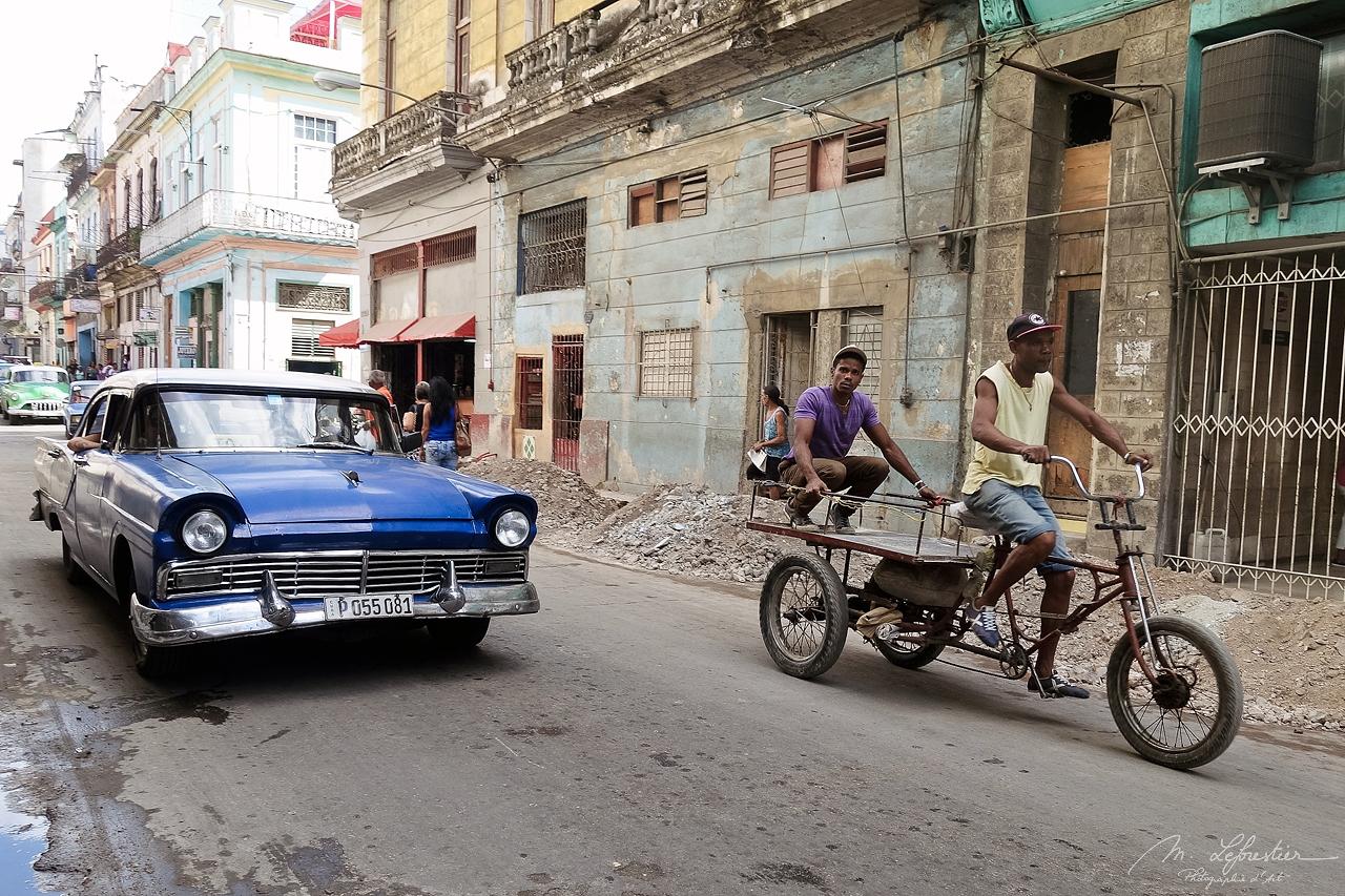 men on a bicyle passing by a blue car in a street of la Havana in Cuba