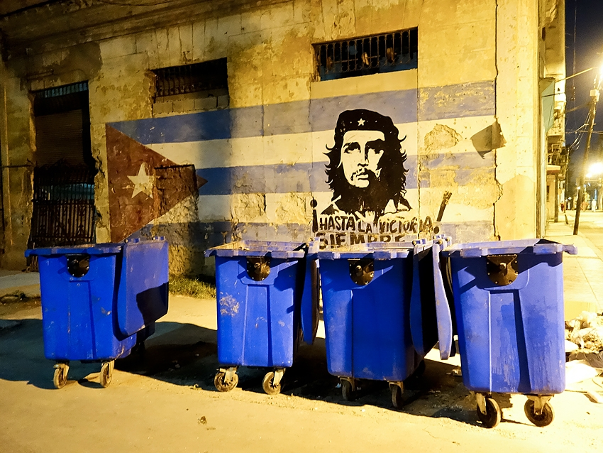 trash bins by night in cuba in front of a painted wall with Che Guevara in la Havana