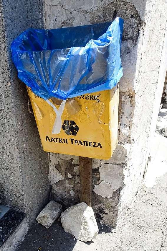 a yellow litter bin in a corner of a street in Lefkara Cyprus